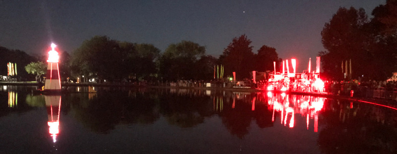 Not terribly good night photo.  Something that may be a red neon lighthouse in the middle of a lake and a red neon structure on the shore.