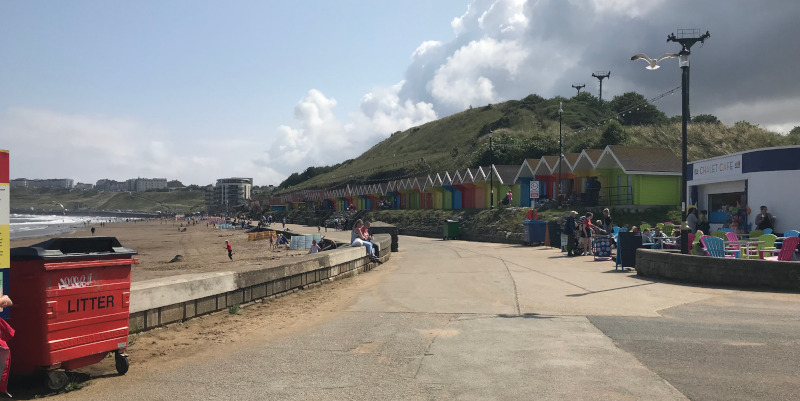 Scarborough Promenade with multi-coloured beach huts on the right and the beach on the left.