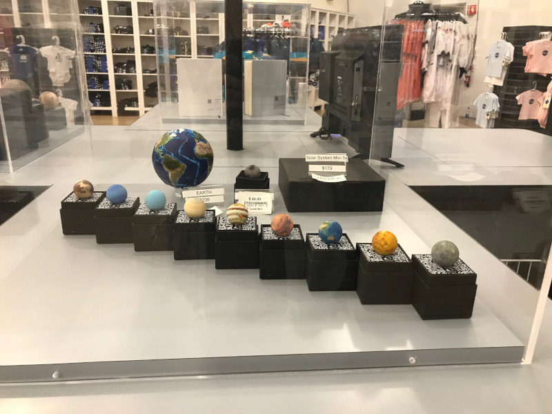 A display case of the planets of the solar system, priced up.  Racks of hoodies and T-shirts visible in the background
