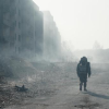 A figure with a backpack moves along a deserted burnt out street from Wendern 2053 from Dark.