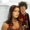 Leela and the Doctor looking at the camera.  Leela stands in front of the Doctor.