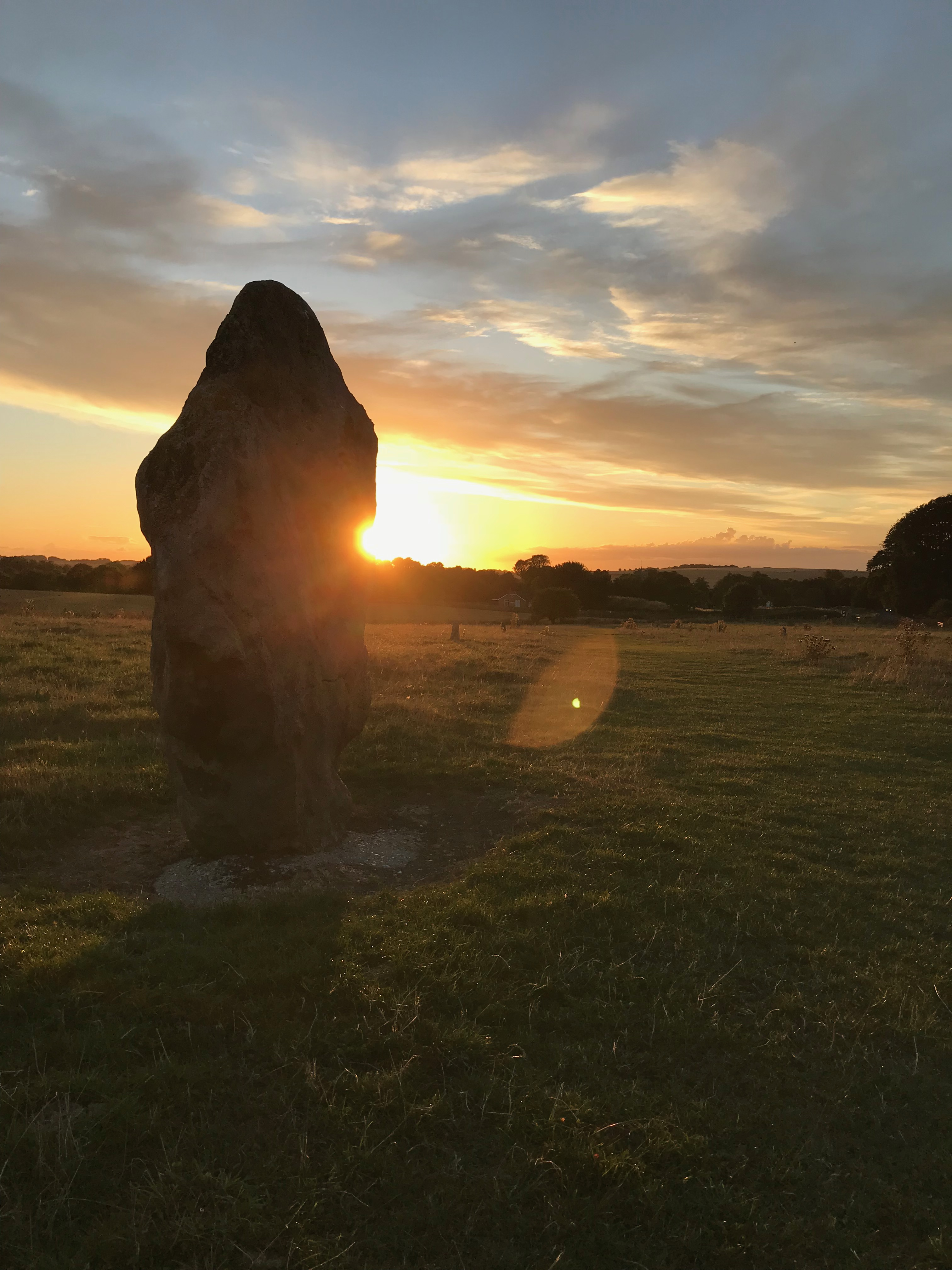 Silhouette of a standing stone with the sun setting just behind it